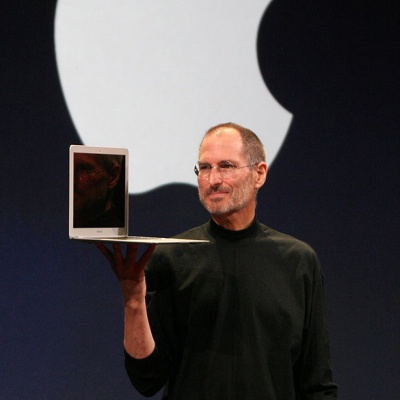 Steve Jobs holding a Mac Book Air