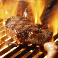 beef steak on the grill with flames