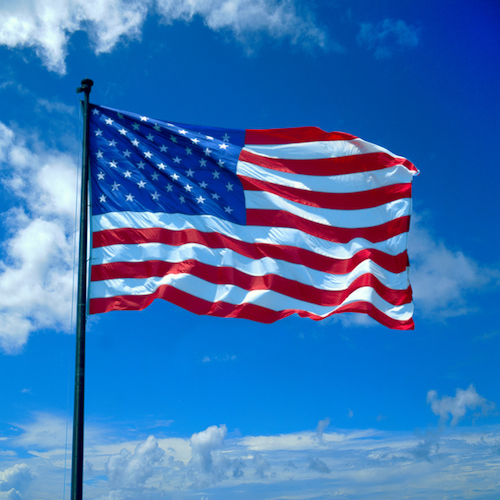 American flag fluttering against cloudy sky, USA
