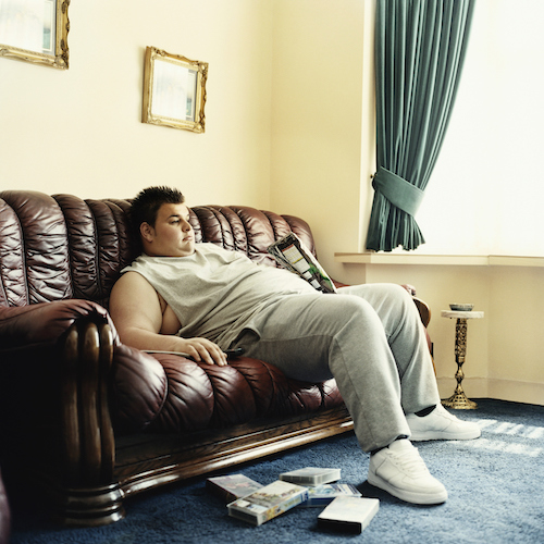 Young Man Lies Slouched on a Sofa Watching Videos and Holding a Packet of Crisps