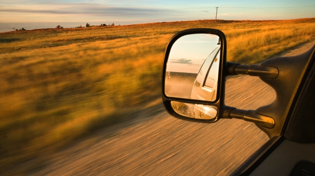 Mirror of car driving through rural fields, North Dakota