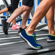 Group of legs wearing sneakers running on treadmill