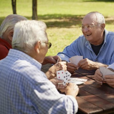 Group of senior men, smiling and playing cards at the park