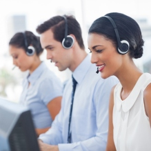 Smiling call center employees sitting in line, good customer service