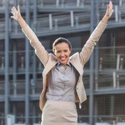 Excited young businesswoman with arms raised standing against office building
