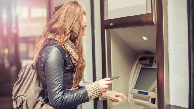 Young woman taking money from ATM, credit card