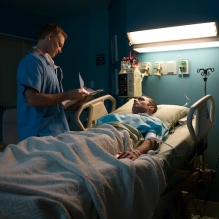 Doctor examining patient in hospital room, sick