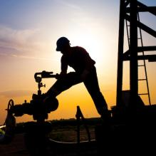 Silhouette of an oil worker using machinery at sunset