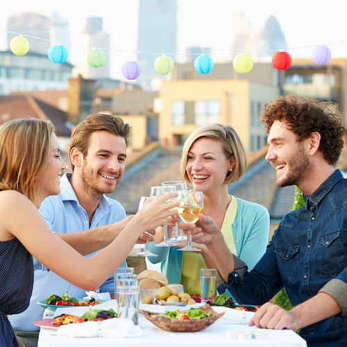 Group Of Friends Eating Meal On Rooftop Terrace, Dinner Party