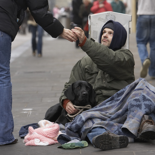 Person giving cup to homeless man, poverty, poor, beggar