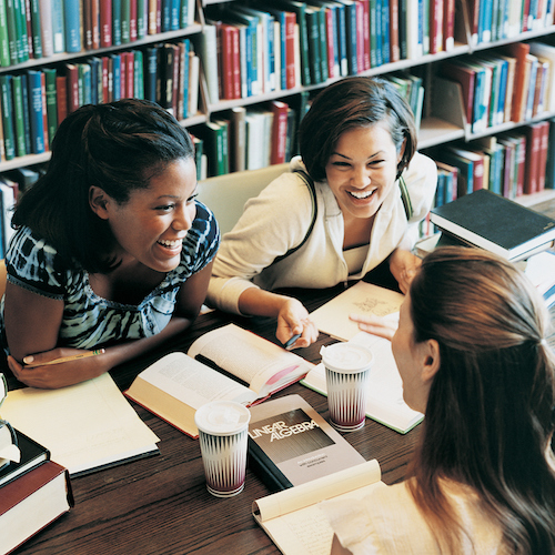 Three Female Students Talking in a Library