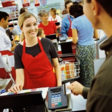 Young man using a credit card machine at a checkout counter in a supermarket