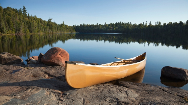 Canoe on rocky shore of calm lake with pine trees Minnesota