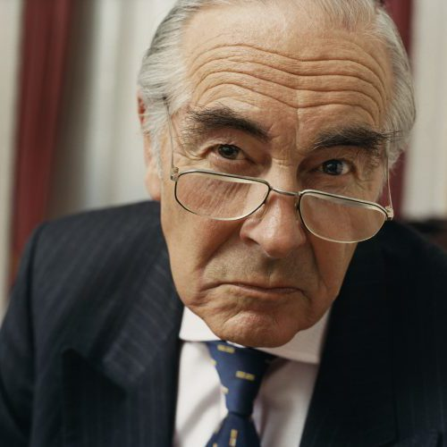 Portrait of a Sulking Businessman Wearing Spectacles and a Pinstripe Suit