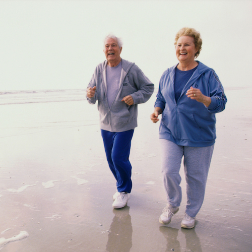 portrait of senior couple jogging on the beach old couple