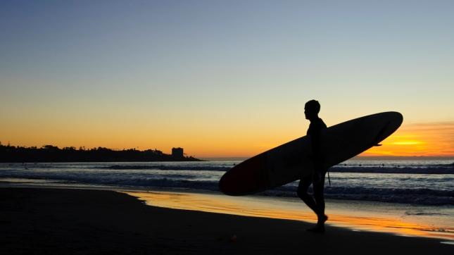 Surfer walking on a beach at sunset San Diego, California