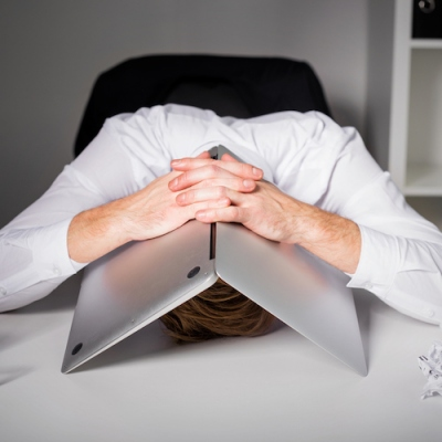 Man hiding under laptop bad business working frustration