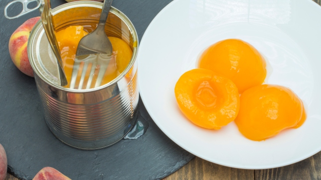 Canned peaches,tin can with preserved peaches, fresh peaches around the canned fruit