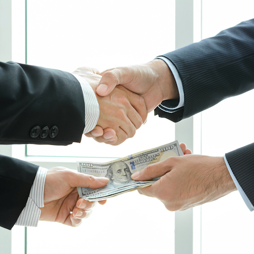 Corruption Businessmen making handshake while passing money