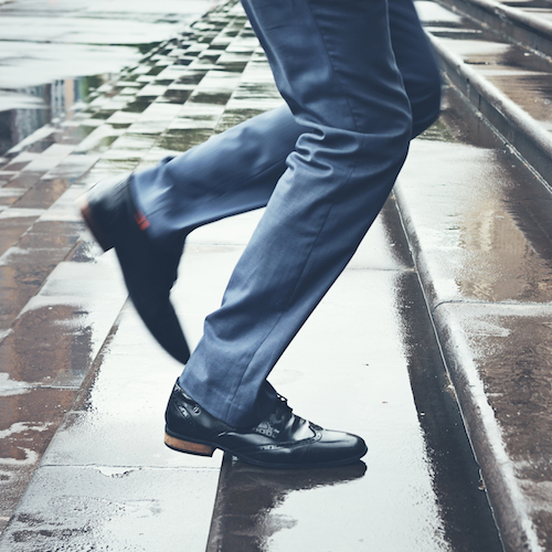 Man in suit running late up steps in rain, walking to work
